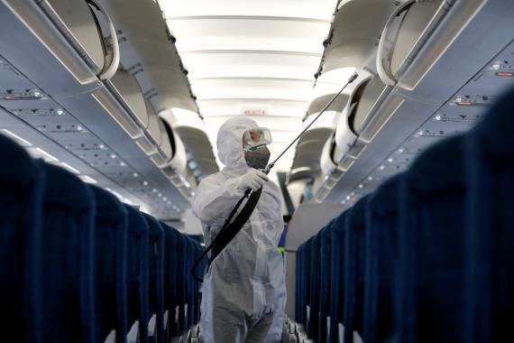 Un trabajador desinfecta un avión por el medio a infecciones por el brote del coronavirus de Wuhan