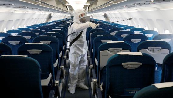 Un trabajador sanitario desinfecta un avión de Vietnam Airlines en el aeropuerto de Hanoi