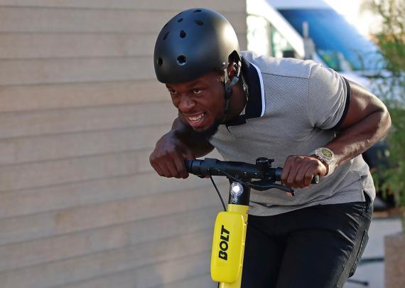El exatleta Usain Bolt conduce un patinete eléctrico compartido de la marca Bolt en París.