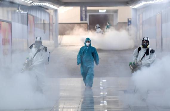 Voluntarios con trajes protectores desinfectan una estación de tren en Changsha, en la provincia china de Hunan.