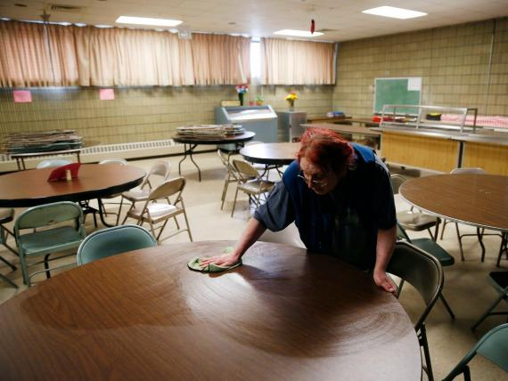 Adrienne Marchetti, executive director of the Pawtucket Soup Kitchen, wipes down tables inside the dining room where meals are served, on March 2, 2020 in Pawtucket, Rhode Island.