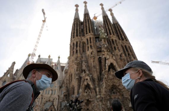 Dos turistas en la Sagrada Familia de Barcelona con mascarillas por el coronavirus.