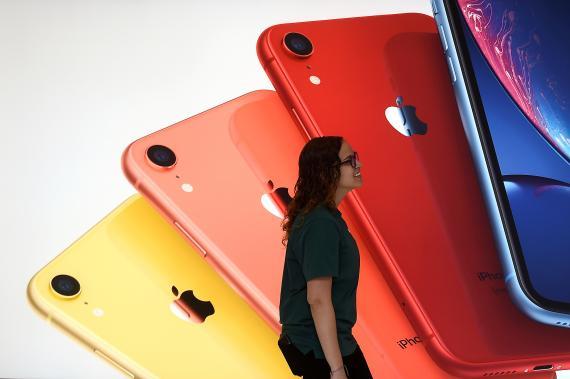 Una empleada de una Apple Store pasa por delante de un mural con los iPhone