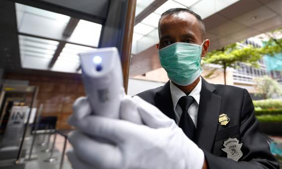 Un empleado de seguridad mide la temperatura a la entrada de un banco en Indonesia