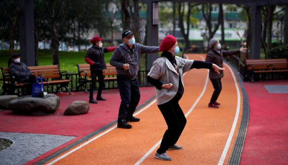 Un grupo de ancianos con mascarillas hacen tai chi en un parque de Pekín