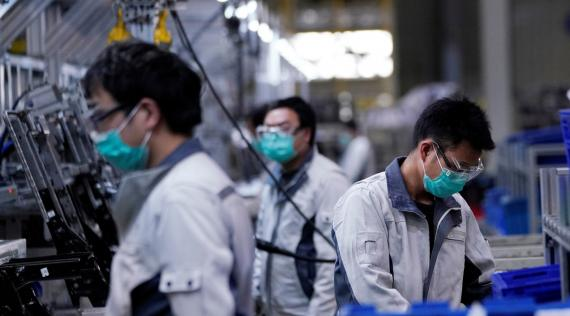 Un grupo de trabajadores de una planta automovilística en Shanghai (China), con mascarillas y gafas protectoras