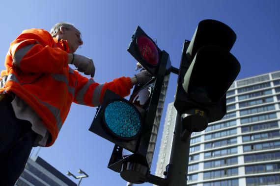 Hombre arreglando un semáforo.