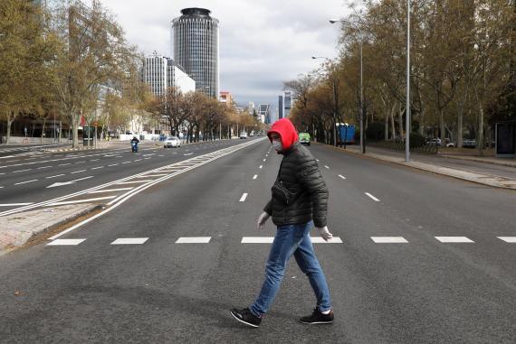 Un hombre cruza el Paseo de la Castellana en Madrid medio de la crisis del coronavirus.