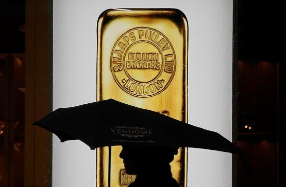 Hombre pasea con un lingote de oro de fondo.