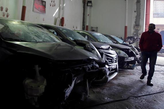 Un hombre pasea por un taller de coches