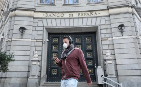 Un joven con mascarilla por el coronavirus camina delante del Banco de España