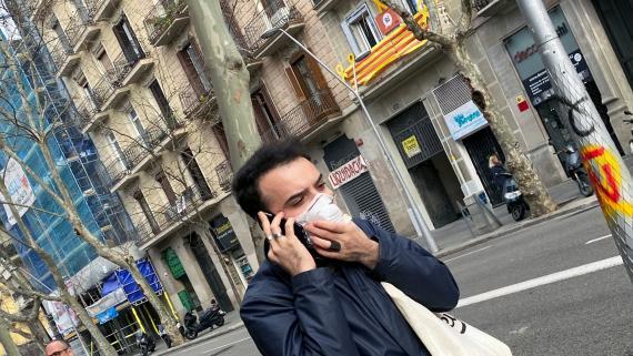 Joven con mascarilla pasea por Barcelona.