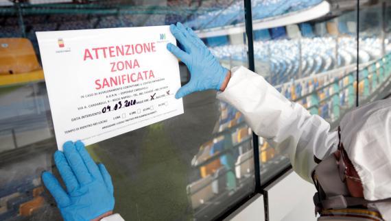 Un limpiador coloca un cartel de desinfección de coronavirus en el Estadio San Paolo de Nápoles