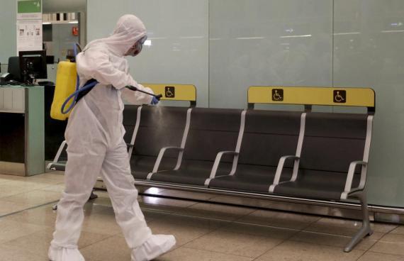 Un miembro de la UME limpia de coronavirus el aeropuerto de El Prat.