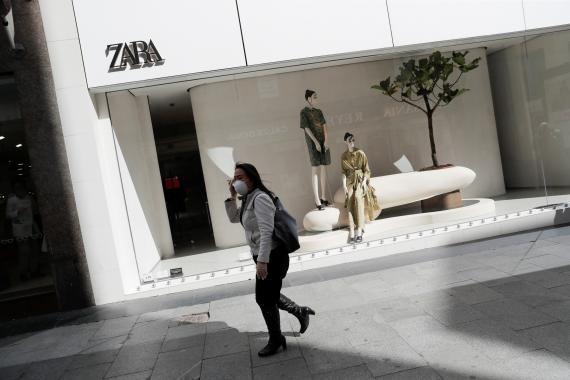 Una mujer con mascarilla camina delante de una tienda de Zara en Madrid durante el periodo de confinamiento.