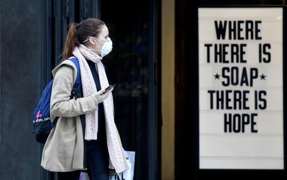 Una mujer con mascarilla pasa por delante de un cartel en la crisis del coronavirus.