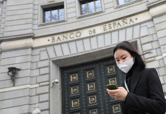 Mujer con rasgos asiáticos en la puerta del Banco de España.
