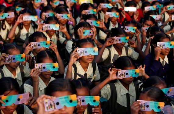 Niños utilizan gafas para ver un eclipse solar en India.