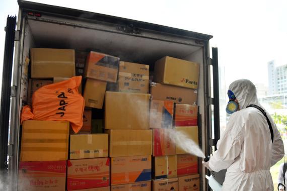 Un operario desinfecta un camión de transporte por el brote del coronavirus