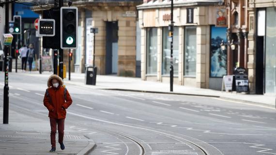 Una persona camina por una calle desierta de Manchester (Reino Unido) durante el brote de coronavirus.