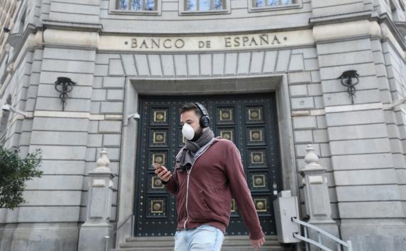 Una persona con mascarilla por el coronavirus camina por Madrid antes del estado de alarma.