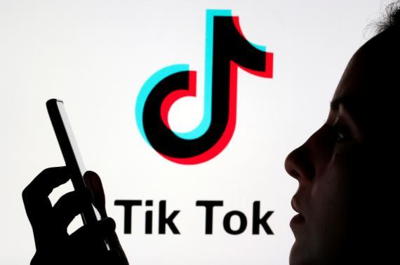 Una persona mira un móvil delante del logo deTik Tok