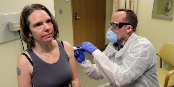 Un farmacéutico le da a Jennifer Haller, izquierda, la primera inyección de la primera etapa del estudio de seguridad de una posible vacuna para COVID-19, la enfermedad causada por el nuevo coronavirus.