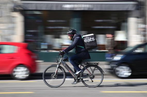 Un repartido de Uber Eats transporta un pedido de comida a domicilio