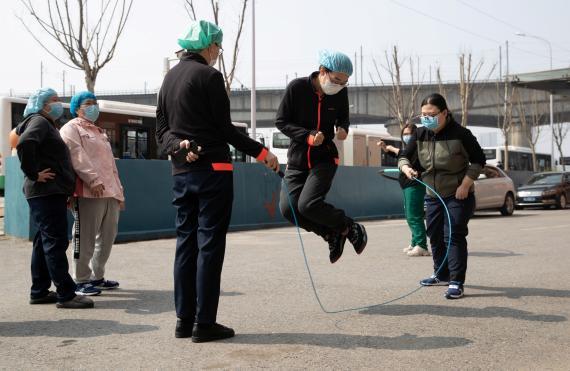 Sanitarios con mascarillas en Wuhan en un descanso a la salida de su hotel