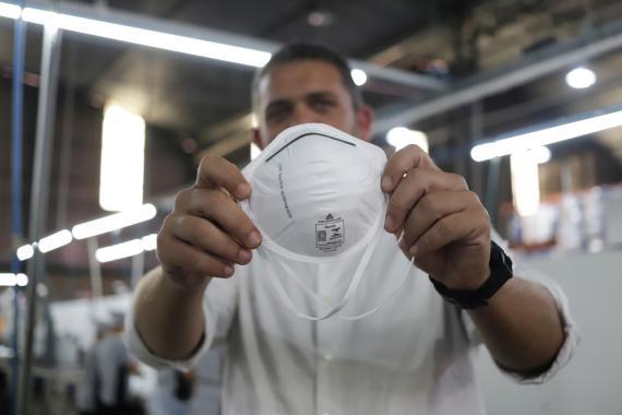Un trabajador se pone una mascarilla para protegerse del brote del coronavirus