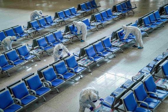 Trabajadores desinfectan estación de tren de Wuhan