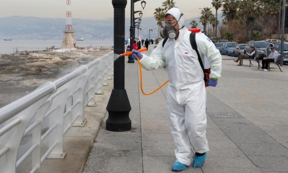 Un trrabajador del Ministerio libanés de Sanidad desinfecta la barandilla del paseo marítimo de Beirut