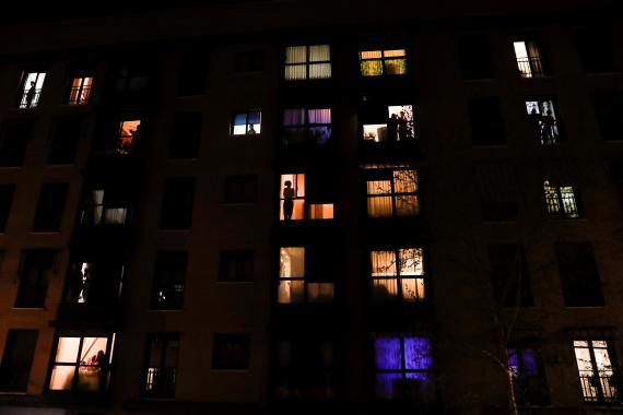 Varios vecinos se asoman a las ventanas de un edificio de pisos en Madrid para aplaudir a los sanitarios en medio de la crisis del coronavirus