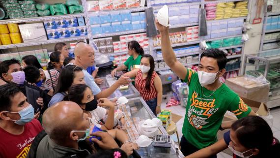 Un vendedor muestra su última máscara disponible en una tienda durante el brote de coronavirus.
