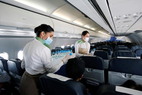 Tripulantes de cabina de pasajeros sirven agua en un vuelo de Bamboo Airway en Vietnam.