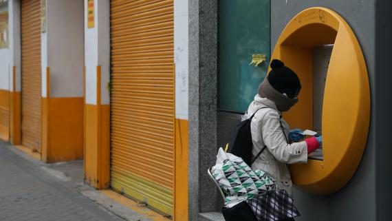 Una mujer usa un cajero automático durante la pandemia de coronavirus en Madrid.