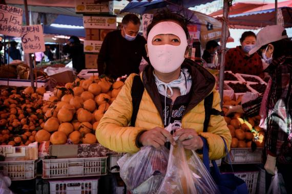 A Chinese woman wears a full face protective mask as she shops at an outdoor food market on April 3, 2020 in Beijing, China.