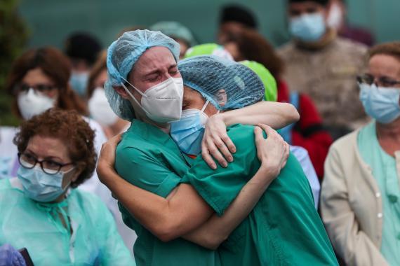 Dos enfermeras se abrazan en la entrada del hospital Severo Ochoa de Leganés durante un homenaje a un compañero que ha fallecido por la pandemia del coronavirus.