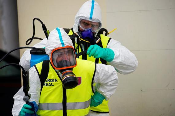 Dos miembros de la Guardia Real se ponen el equipamiento para protegerse del coronavirus.