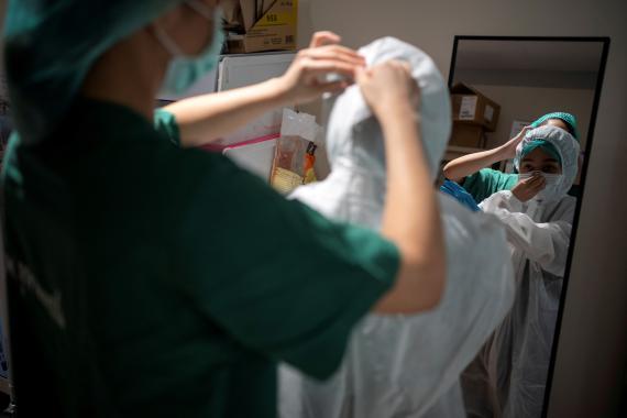 Una enfermera se coloca un traje protector en medio de la pandemia del coronavirus