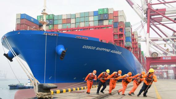 Estibadores del puerto de Qingdao ayudan en el atraque de un carguero