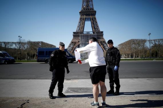 Gendarmes franceses al pie de la Torre Eiffel comprueban el justificante de un ciudadano en la calle en pleno confinamiento