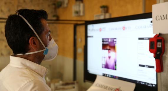 Un hombre delante de un ordenador con mascarilla por el coronavirus.