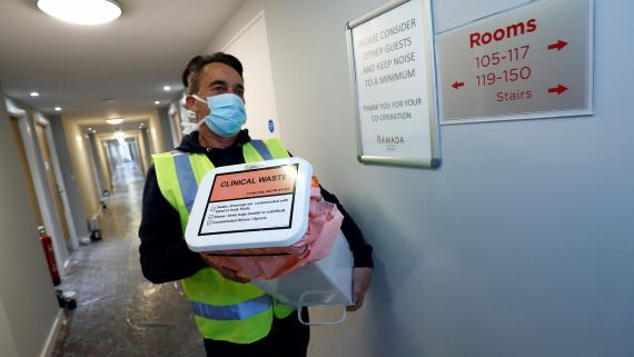 Un hombre con mascarilla lleva material sanitario en los pasillios de un hotel.