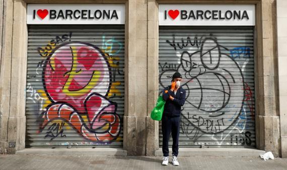 Un hombre con mascarilla, ante una tienda de souvenirs cerrada en Barcelona