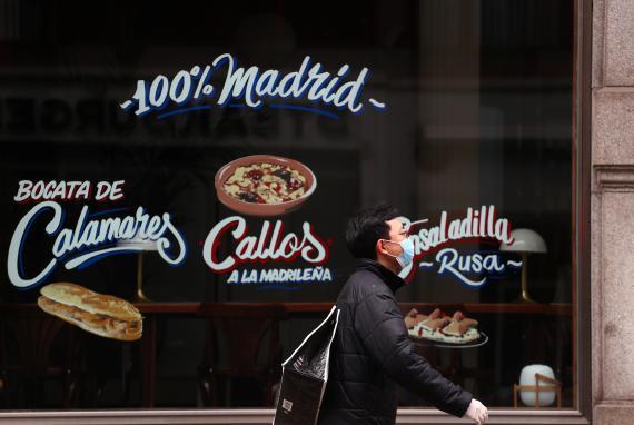 Un hombre pasa con una mascarilla para protegerse del coronavirus por delante de un restaurante.