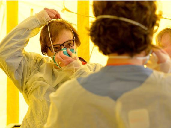 Sanitarios poniéndose equipos de protección antes de examinar a pacientes posibles casos de coronavirus en el Hospital Newton-Wellesley de Newton, Massachusetts, EEUU.