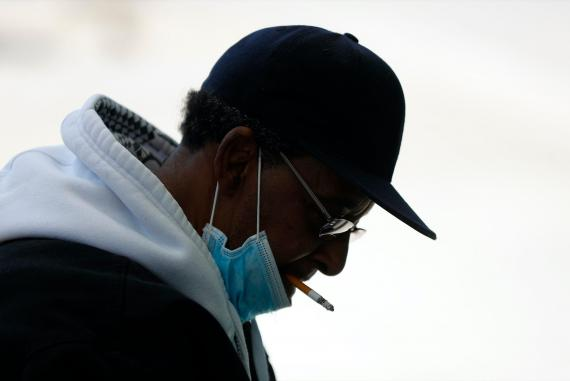A man smokes a cigarette while wearing a protective mask while waiting for a bus in Detroit, Wednesday, April 8, 2020.