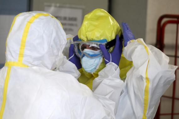 Miembros del SUMMA se equipan con trajes protectores antes de visitar a un paciente con coronavirus