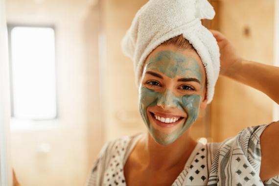 Una mujer se aplica un producto de belleza.